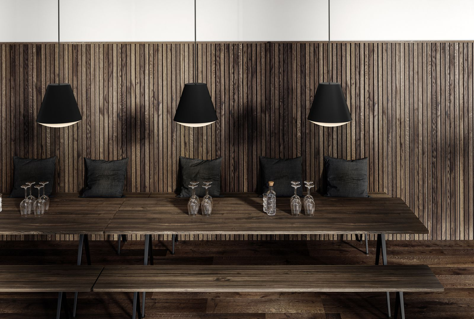 Dining area with long dark wooden tables and benches and black pendant lamps in Nordic Dark