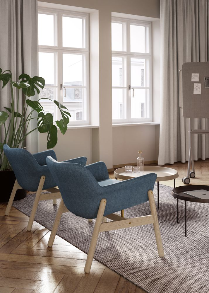 Executive office lounge area with blue accented lounge chair and coffee table in Nordic Light