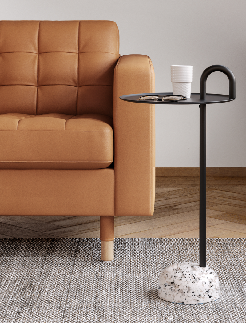 Lounge chair with comfortable cushions and a black bowler side table in Nordic Light