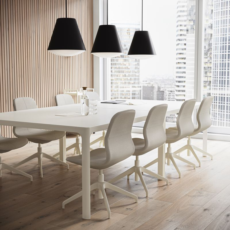 Meeting room with white tables, beige office chairs and black pendant lamps in Nordic Light