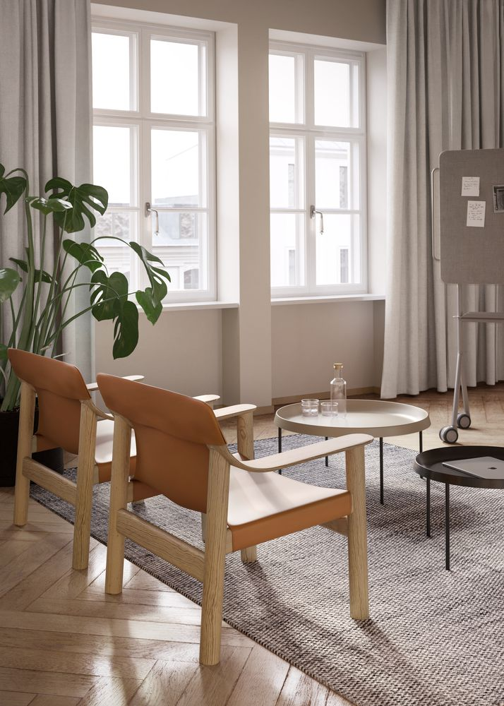 Lounge area in an executive office with brown lounge chairs, wooden coffee tables and beige curtains in the setting Nordic Light