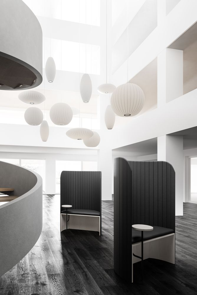 Open lounge area with dark wooden features and white highlights on the facade in Nordic Black & white including focus work pods featuring Zilenzio shields
