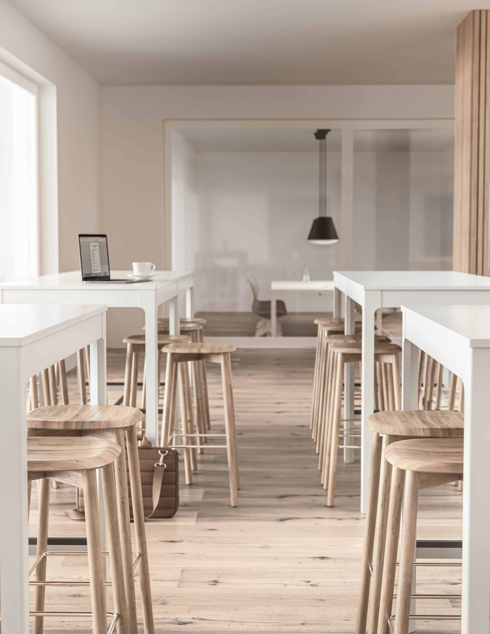 Lounge area with beautiful wooden details, white tables and wooden tall stools in Nordic Light