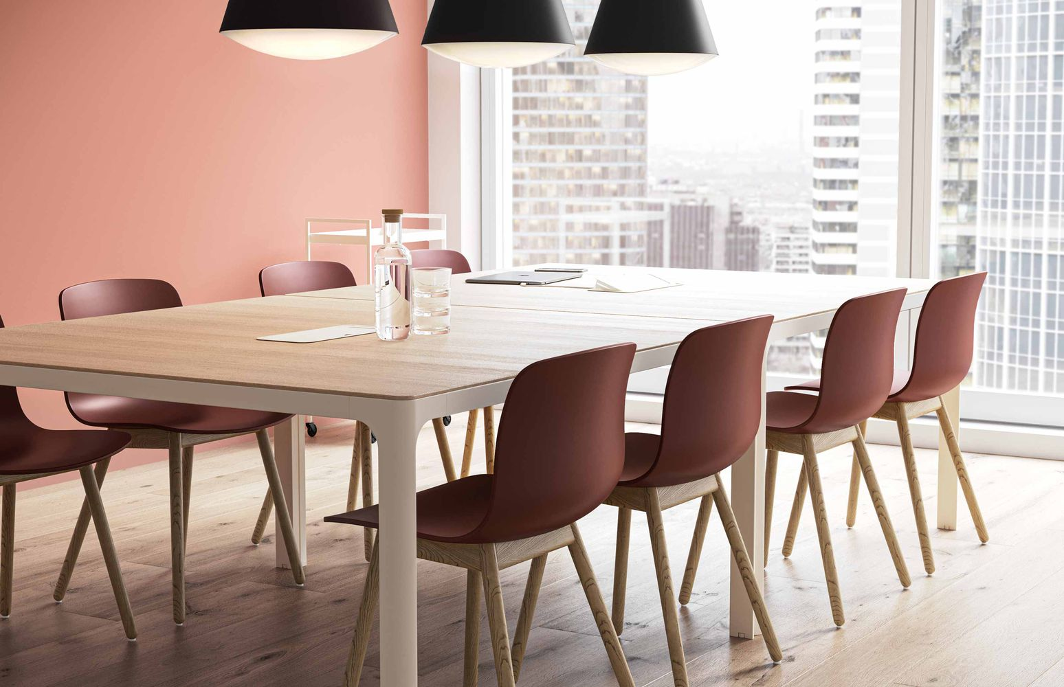 Meeting room with red accented chairs, wooden desk and pastel pink walls in Nordic Light