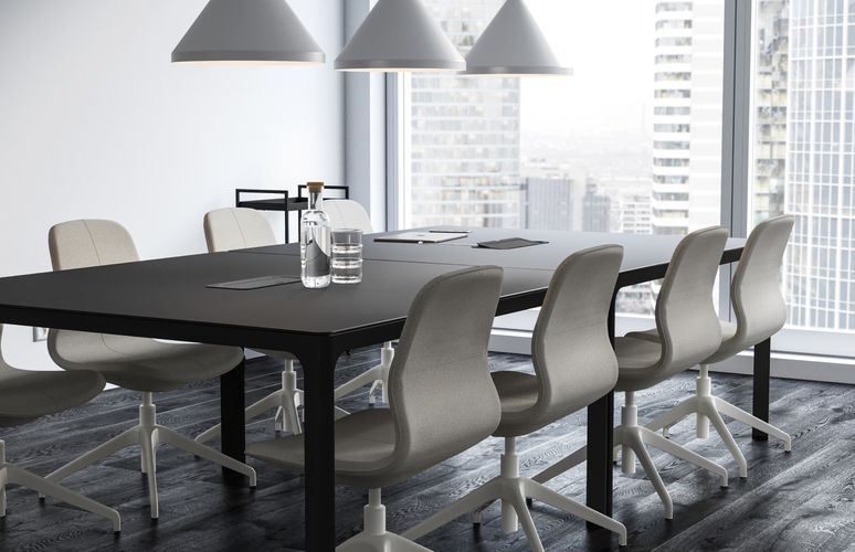 Meeting room with beige chairs and white pendant lamps, black wooden tables and Black floors.