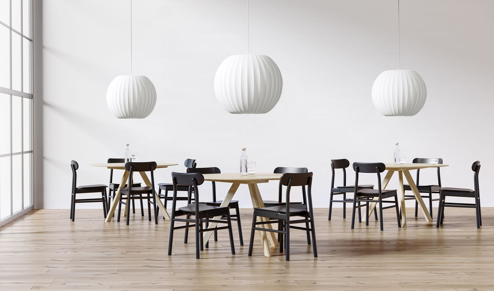 Dining area with light wooden round tables and dark chairs in Nordic Light.JPG