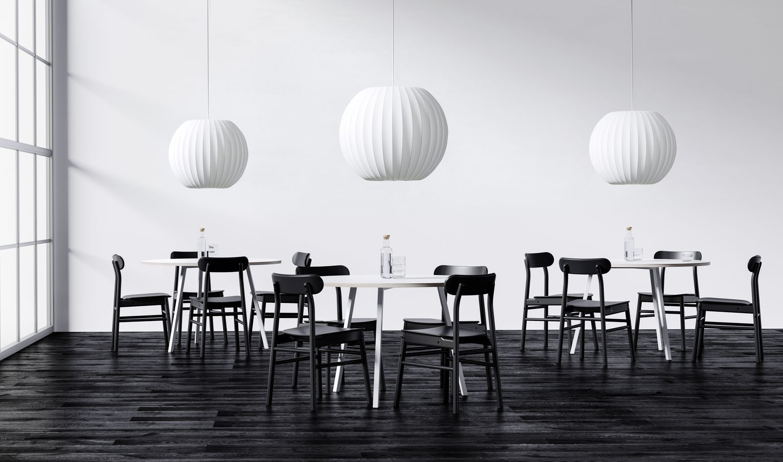 Dining area with white round tablles and black wooden chairs and white lamps in Nordic Black & White.jpg