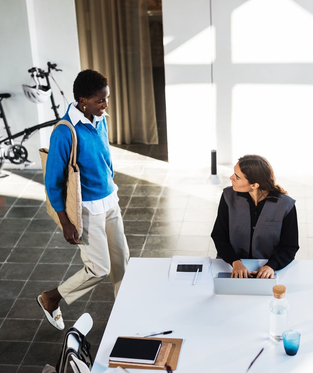 Colleagues greeting each other beside a white desk and brompton bicycle.