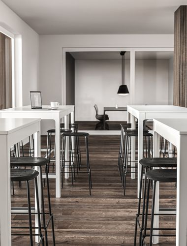 Lounge area with white tall standing tables and bar chairs in Nordic Black & White.jpg