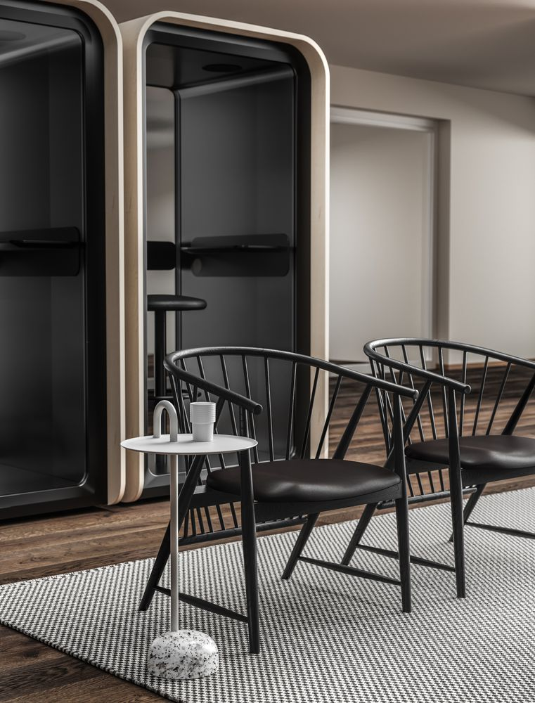 Lounge area with wooden lounge chairs, designer side table and phone booths in Nordic Dark.jpg