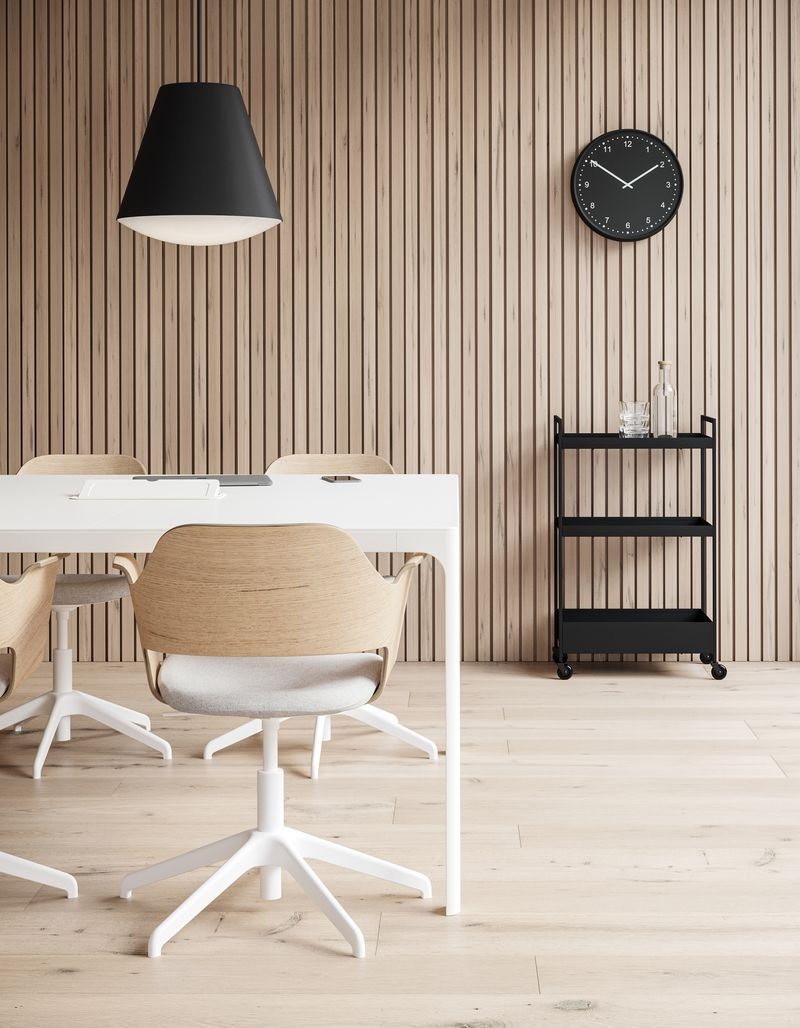 Meeting room with wooden wall panels, black pendant lamps, clock and office chairs in Nordic Light setting