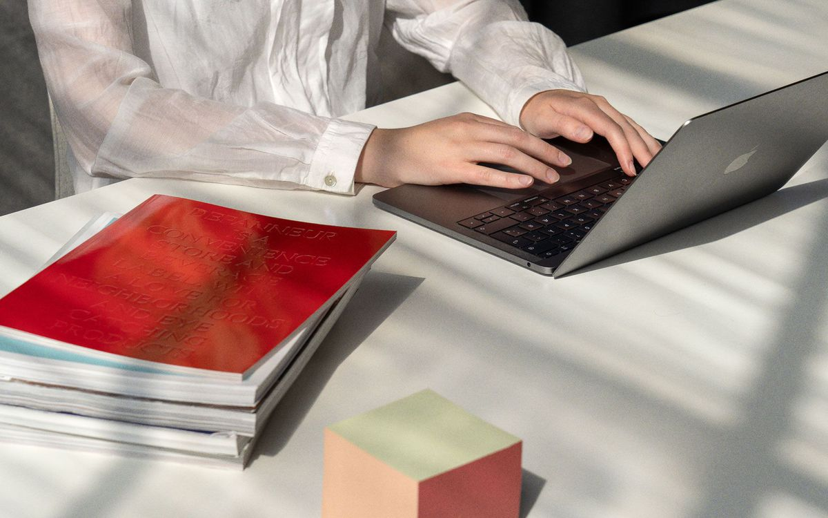 Employee working on a White Desk with stacks of books beside.