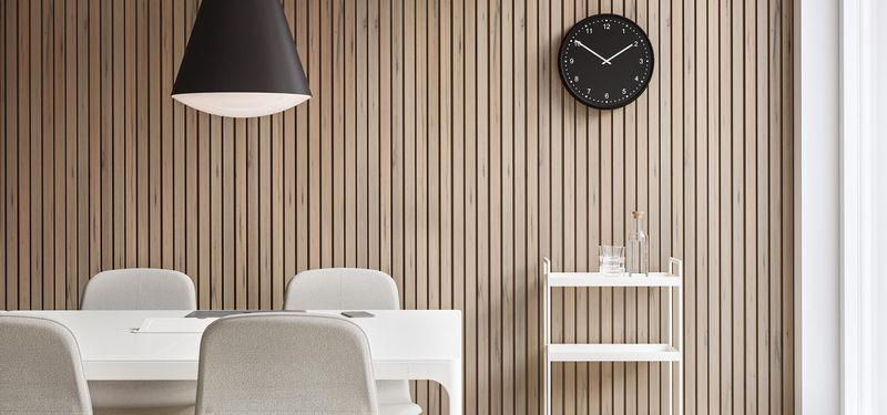 News Page - Meeting room with wooden accents and white tables and beige chair, with clock on the wall and a white bar counter in Nordic Light