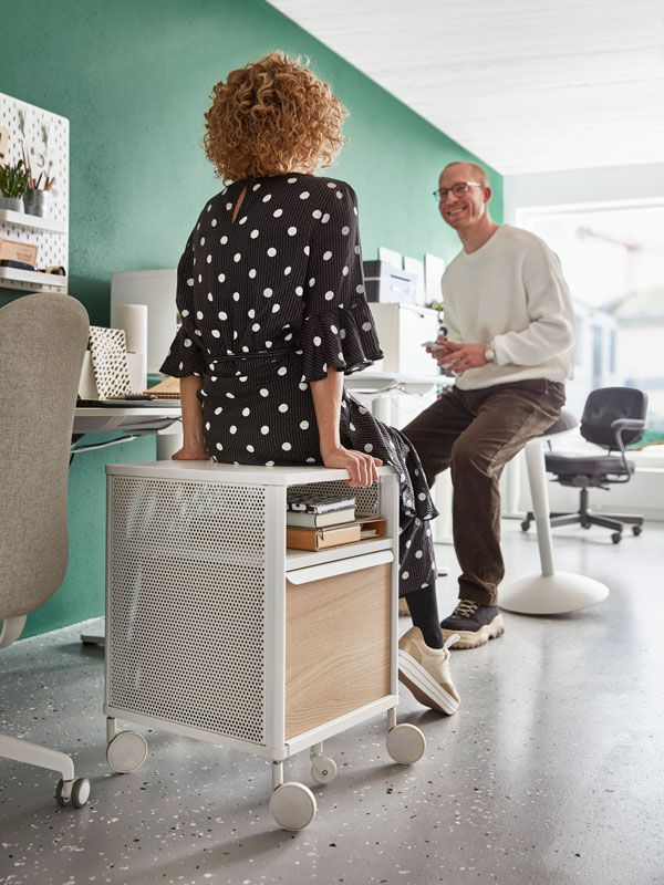 Man sitting on bar chair and woman sitting on desk cabinet in a discussion
