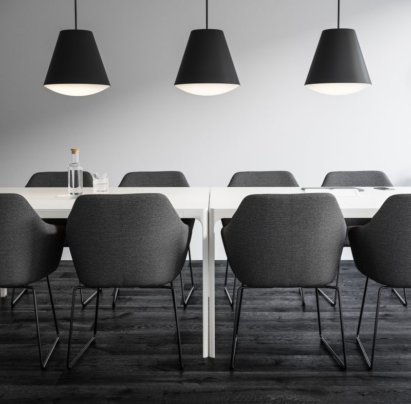 Meeting room with white table and grey chairs and black pendant lamps in Nordic Dark setting